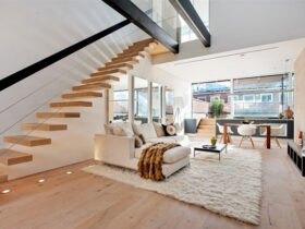 نشیمنی با مبل ال و فرش کرم رنگ، کفپوش چوبی و پله معلق چوبی