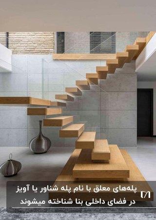 پله معلق چوبی با حفاظ شیشه ای در خانه با دو دکوری استیل زیر پله