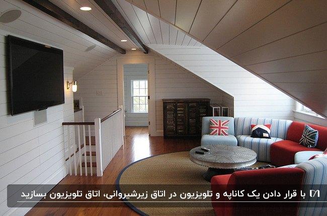 دکوراسیون اتاق تلویزیون زیرشیروانی با مبل منحنی آبی و قرمز، کوسن های طرحدار و تلویزیون روی دیوار