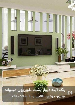 اتاقی با دیوار سبز پشت تلویزیون با آینه کاری های مستطیلی