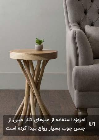 یک میز کنار مبلی گرد چوبی با پایه بلند بعنوان وسایل چوبی تزئینی