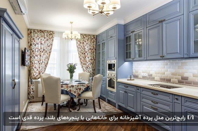 آشپزخانه ای با کابینت های آبی و پرده آشپزخانه گلدار قدی