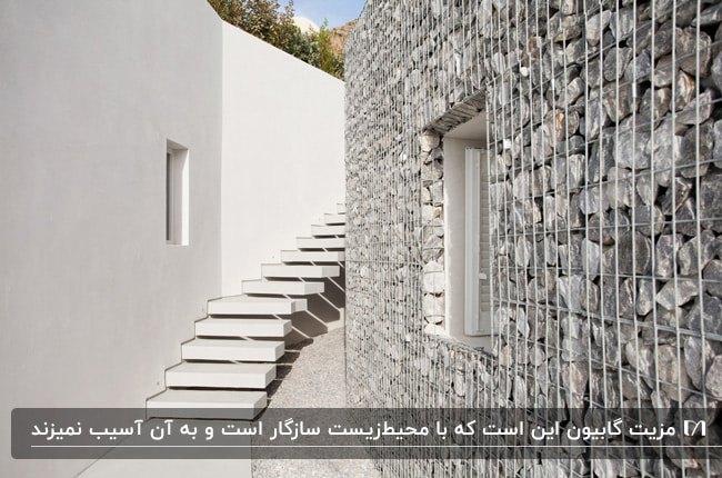 راهرویی با پله های سفید،دیوار سیمانی سفید و یک دیوار گابیونی