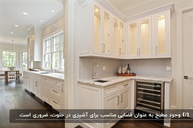 آشپزخانه مطبخ داری با کابینت های سفید و کفپوش قهوه ای تیره