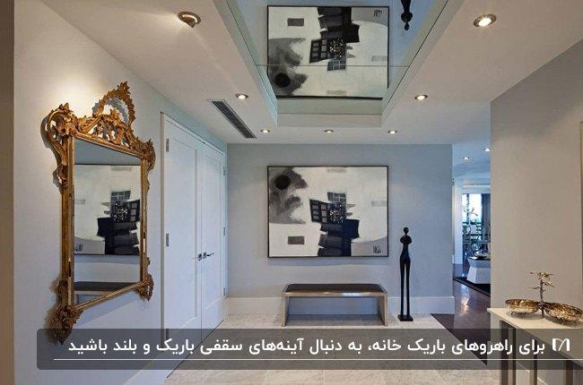 راهرویی با دیوارهای طوسی، تابلو و آینه روی دیوار و سقف آینه کاری شده
