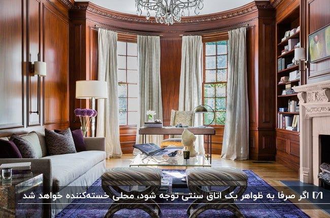 دکوراسیون داخلی سنتی نشیمنی با دیوارپوش چوبی، مبل طوسی، کوسن ها و فرش بنفش