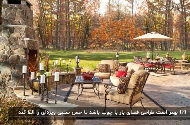 دکوراسیون داخلی سنتی فضای باز خانه ای با میز و صندلی های فرفورژه ،تشکچه های کرم و کوسن های قرمز