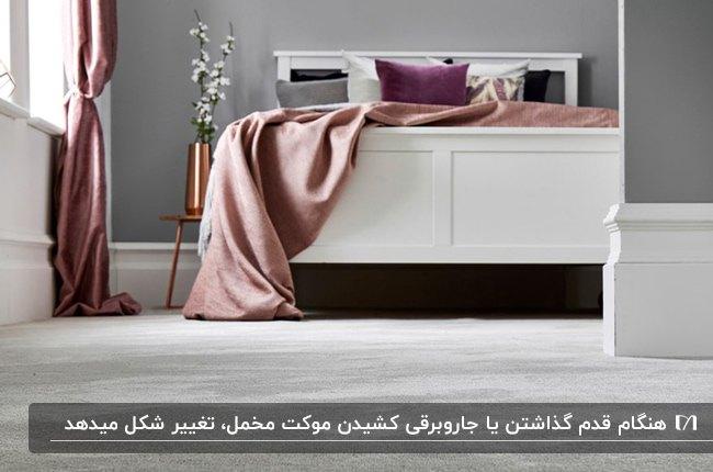 اتاق خوابی با تخت دو نفره سفید، روتختی صورتی و بنفش، دیوارها و موکت مخمل طوسی رنگ