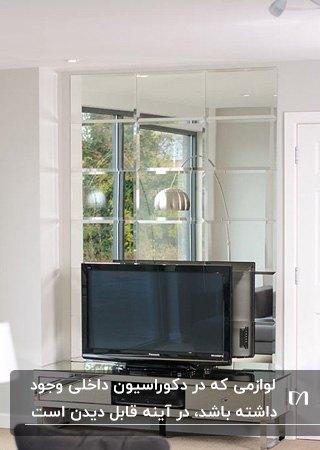 اتاقی با دیوارهای سفید و آینه کاری دیوار پشت تلویزیون