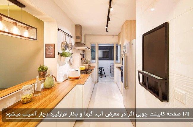 آشپزخانه باریک و درازی با کابینت های سفید و صفحه کابینت چوبی قهوه ای