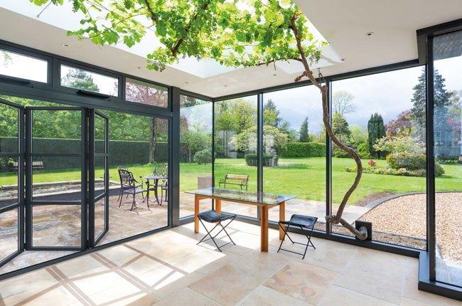 اتاق کاری با دیوارها و سقف شیشه ای، میز و صندلی های کار و درب تاشو