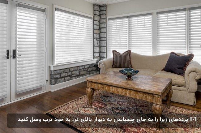 پرده زبرای سفید برای درب ورودی . پنجره های نشیمنی با مبل کرم و میز چوبی مربعی