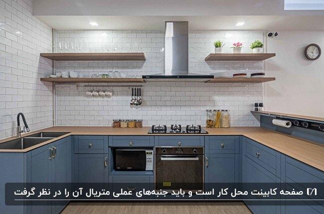 آشپزخانه ای با کابینت های آبی، صفحه کابینت چوبی قهوه ای و قفسه های دیواری چوبی