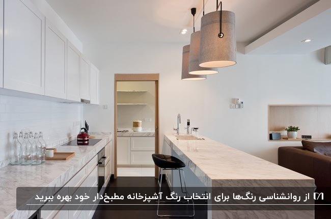 آشپزخانه مطبخ داری با کابینت های رنگ سفید، کفپوش قهوه ای تیره و سه لوستر آویز