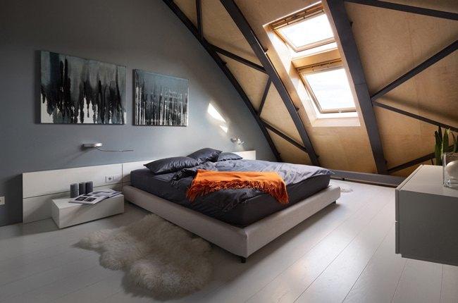 دکوراسیون اتاق زیرشیروانی با دیوار طوسی، تخت سفید و سقف شیبدار چوبی و فلزی