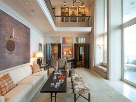 دکوراسیون خانه دوبلکسی با مبلمان و پاف کرم و قهوه ای، آباژور لوستر آویز با دیوار شیشه ای