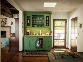 کافی بار خانگی با کابینت ها و قفسه های سبز رنگ نزدیک درب ورودی در خانه ای سنتی