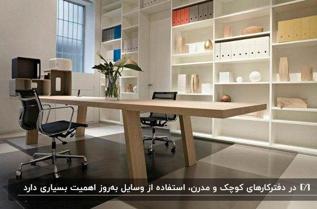 دفترکار کوچک و مدرنی با قفسه های دیواری سفید، میز مستطیلی چوبی و صندلی های مشکی