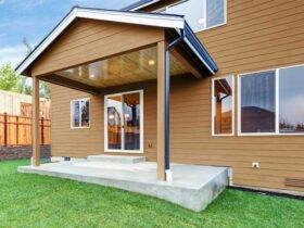 نمای خارجی خانه ای ویلایی با فریم های سفید درب و پنجره و دیوارپوش کامپوزیتی قهوه ای رنگ