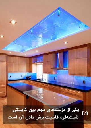 آشپزخانه ای با کابینت های قهوه ای، صفحه رویی مشکی و سقف و بین کابینتی شیشه ای آبی رنگ