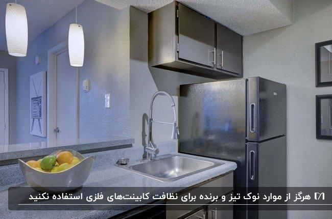 آشپزخانه ای با لوازم برقی نقره ای و کابینت فلزی براق