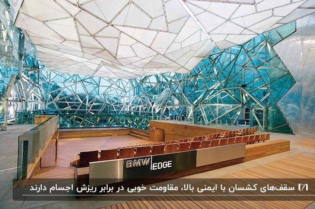 سالنی با صندلی های قهوه ای، دیوارهای کاذب آبی و سقف کشسان سفید