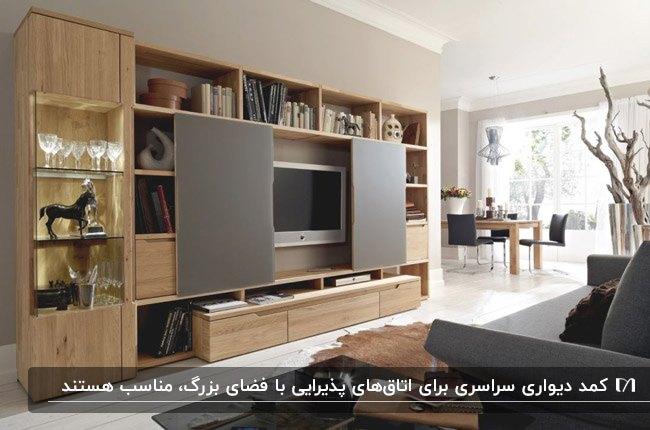 یک اتاق پذیرایی با کمد دیواری سرتاسری رنگ چوب و خاکستری با دکوری
