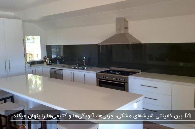 آشپزخانه ای با کابینت ها و کانتر سفید و بین کابینتی شیشه ای مشکی