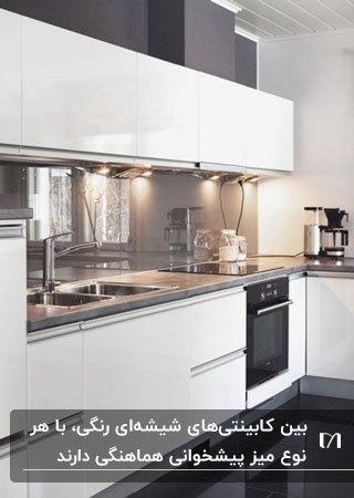 آشپزخانه ای با کابینت سفید، کفپوش مشکی و بین کابینتی شیشه ای خاکستری