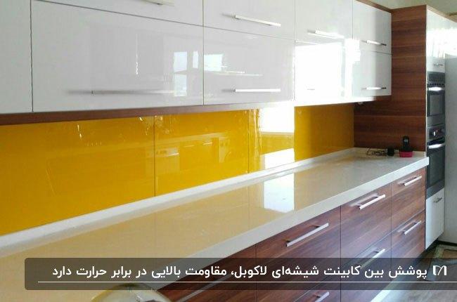 آشپزخانه ای با کابینت های سفید و رنگ چوب و بین کابینتی شیشه ای زرد رنگ
