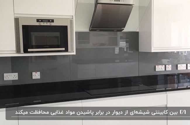 آشپزخانه ای با کابینت های سفید و بین کابینتی شیشه ای مشکی و خاکستری