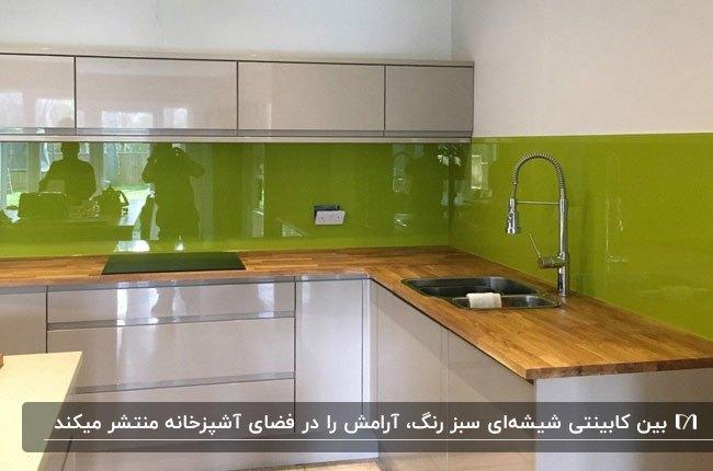 آشپزخانه ای با کابینت های سفید، صفحه رویی کابینت چوبی و بین کابینتی شیشه ای سبز رنگ