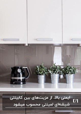 آشپزخانه ای با کابینت های سفید و بین کابینتی شیشه ای لمینتی قهوه ای رنگ