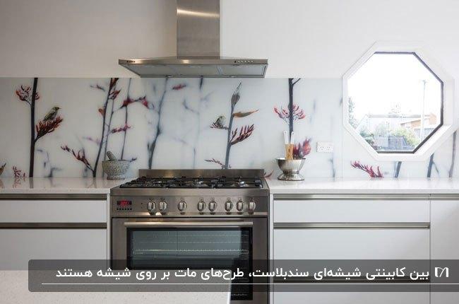 آشپزخانه ای با کابینت های سفید، پنجره هشت ضلعی و بین کابینتی شیشه ای با طرح شاخه گل و پرنده