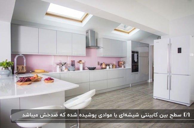 آشپزخانه ای با کابینت های سفید، پنجره های سقفی و بین کابینتی شیشه ای ضدآب صورتی