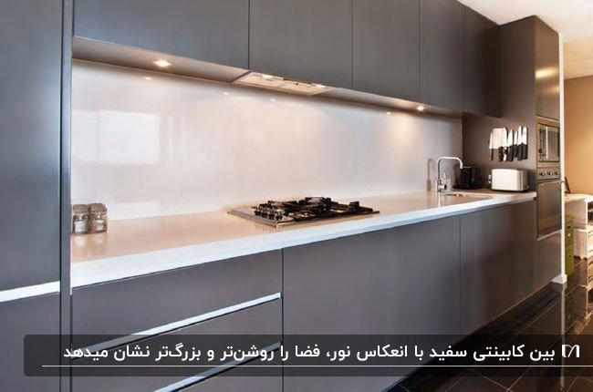 آشپزخانه ای با کابینت های خاکستری و بین کابینتی شیشه ای سفید رنگ