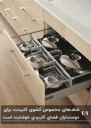 آشپزخانه با کابینت های رنگ چوب و شلف داخل کشوی کابینت