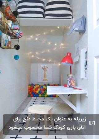 اتاق بازی کودک زیر پله با قفسه و میز دیواری سفید، چهارپایه و ریسه نوری