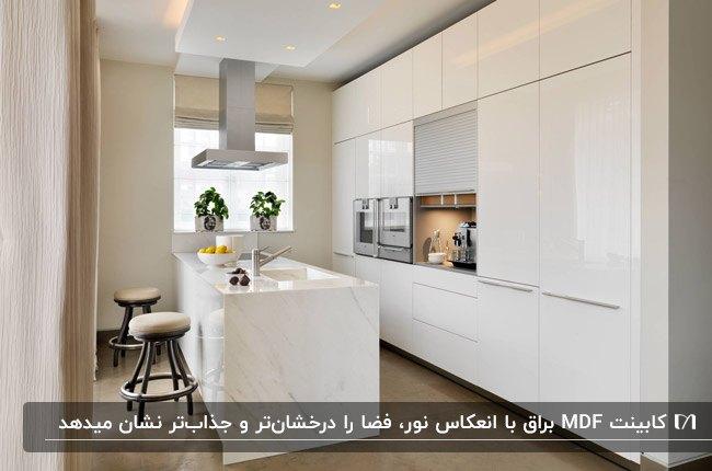 آشپزخانه ای با کابینت MDF سفید براق و جزیره سنگی سفید با رگه های طوسی
