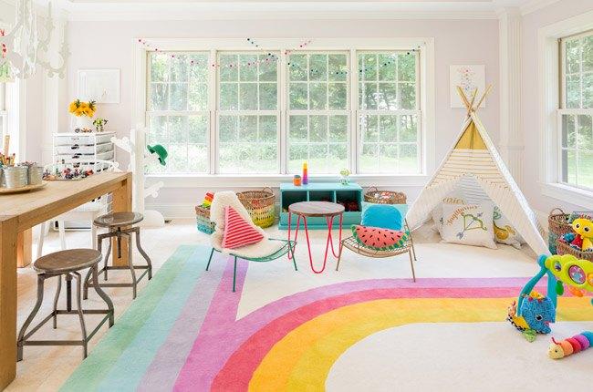 اتاق بازی کودک با پنجره های بزرگ، چادر بازی سفید و فرش طرح رنگین کمان