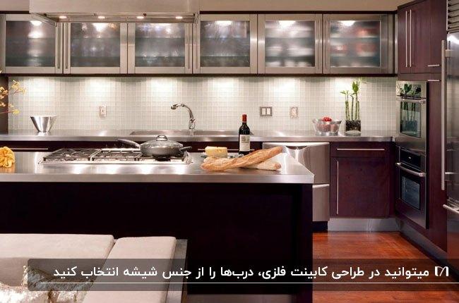 آشپزخانه ای با ترکیب شیشه و فلز برای کابینت با سقف نورپردازی شده
