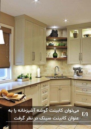 آشپزخانه ای با کابینت های کرم رنگ و کابینت گوشه به عنوان سینک ظرفشویی