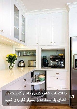 آشپزخانه ای با کابینت های سفید و شلف داخل کابینت گوشه ای چرخان