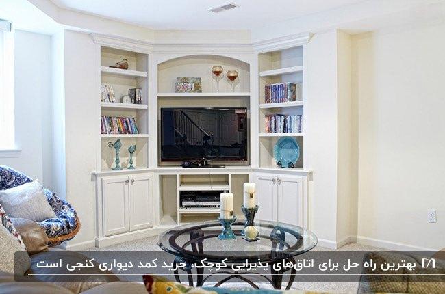 اتاق نشیمنی با کمد دیواری کنجی سفید رنگ و قفسه های کتاب و یک میز عسلی گرد برای جلوی مبل