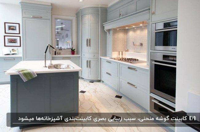 آشپزخانه بزرگی با کابینت های طوسی با نورپردازی و کابینت گوشه منحنی