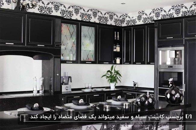 آشپزخانه ای با کاغذدیواری طرحدار سفید و مشکی و برچسب کابینت مشکی