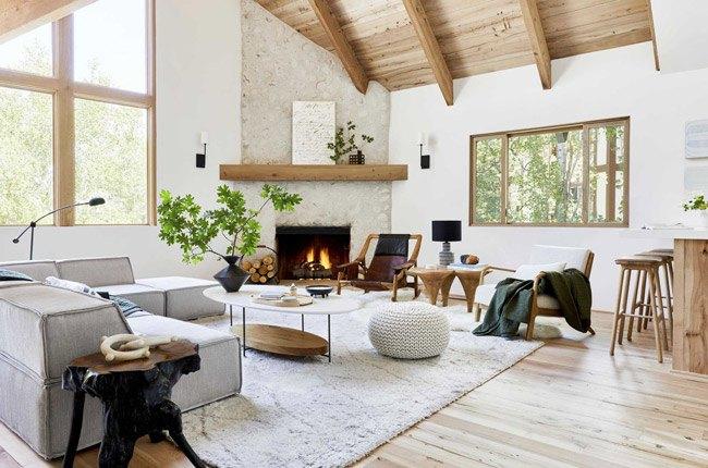 ایده دکوراسیون داخلی نشیمنی با مبل طوسی، شومینه، سقف و کفپوش چوبی و فرش خزدار سفید