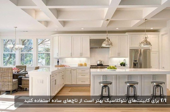 آشپزخانه با کابینت نئوکلاسیک ال شکل و جزیره به رنگ طوسی و سفید