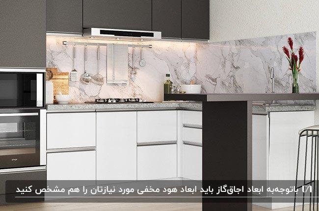 آشپزخانه ای با کابینت های سفید و خاکستری، بین کابینتی طرح سنگ و هود مخفی