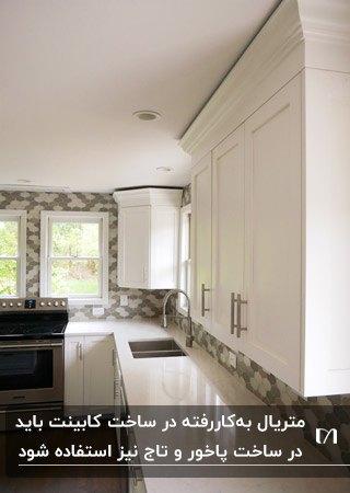 اجزای اصلی کابینت هاس سفید در آشپزخانه ای با بین کابینتی طرحدار و تاج کابینت
